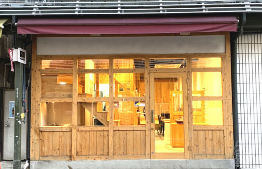 Front of VEGAN STORE in Asakusa Tokyo Japan. A wooden store front with large windows lets you see into a warmly lit dining area and a staircase leading up.