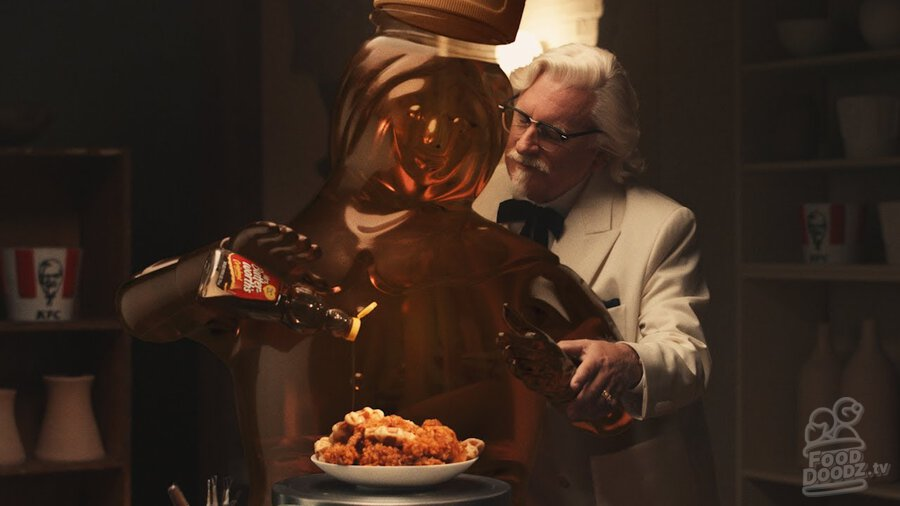 KFC (Kentucky Fried Chicken) Colonel Sanders stands behind Mrs. Butterworth while she pours syrup on a plate of chicken and waffles